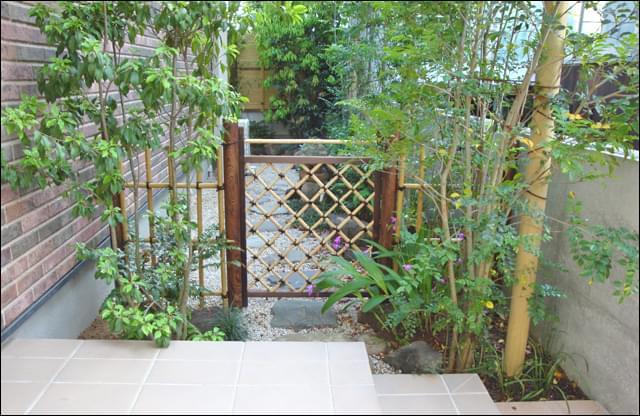 四つ目垣と枝折り戸が迎え、茶庭を思わせる庭デザイン