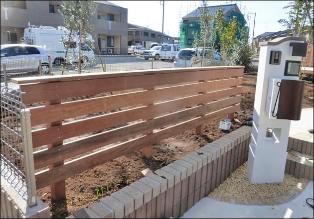 システム門柱の背景としてローウッドフェンスを設置