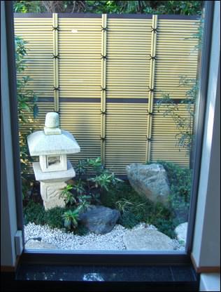 背景に目隠しの垣根を持つ坪庭