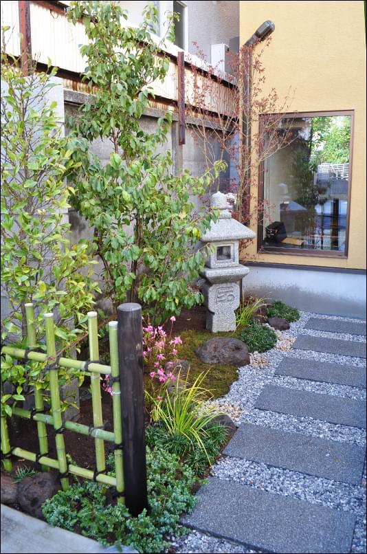 アプローチの敷石と調和する和の庭