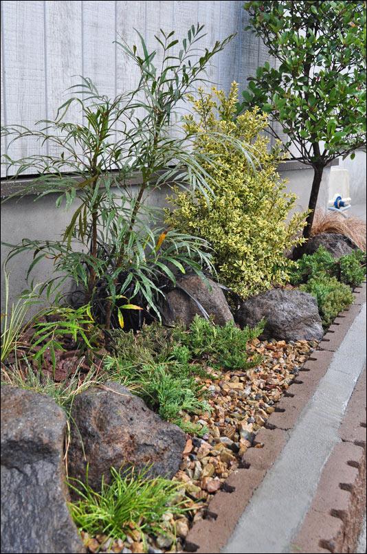 低木と共に動きを感じさせる自然石